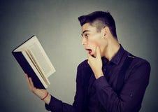 Amazed shocked man reading a book. Isolated on gray background Royalty Free Stock Photo