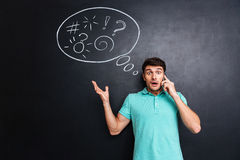 Amazed shocked man talking on mobile phone over blackboard background Stock Photo