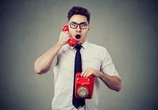 Amazed shocked man talking on a telephone. Amazed shocked young business man talking on a telephone feeling impressed Stock Image