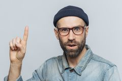 Amazed shocked man wears rectangular spectacles, looks with suprised expression, raises fore finger, has hush reaction, isolated o stock photo