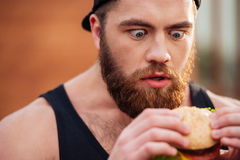 Amazed shocked young man holding and looking at hamburger outdoors. Closeup of amazed shocked bearded young man holding and looking at hamburger outdoors Royalty Free Stock Image
