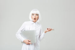 Amazed shocked young woman holding laptop and cell phone. Over white background royalty free stock photos