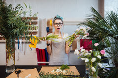 Amazed shoked woman florist holding two bunches of flowers Stock Photography