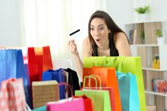 Amazed shopper looking at multiple purchases. In colorful shopping bags at home Royalty Free Stock Image