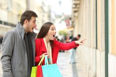 Amazed shoppers finding sales in a storefront. In a big city avenue stock images