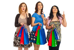 Amazed shoppers women looking up. Three amazed shoppers women with shopping bags looking and pointing up isolated on white background Stock Photography
