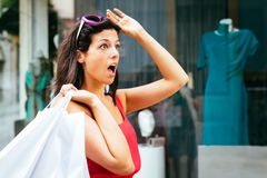 Amazed shopping woman. Jaw dropping woman looking amazed about shopping dress sales Royalty Free Stock Photos