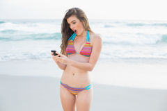 Amazed slim brown haired model in coloured bikini looking at her mobile phone Royalty Free Stock Images