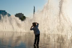 Amazed small boy on a background of a giant wave on the city coast at sunset Stock Photography