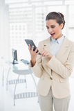 Amazed smart brown haired businesswoman using a calculator. In bright office Stock Photos