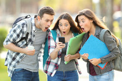 Amazed students checking content on a phone Stock Photos