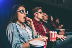 Amazed and surprised people are sitting in one row and watching movie. Blonde girl is eating popcorn with amazement on royalty free stock image