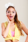 Amazed surprised pin up girl with mouth wide open. Portrait of astonished young woman with bow Stock Photography