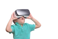 Amazed teen boy wearing virtual reality goggles watching movies. Or playing video games, isolated on white. Surprised teenager looking in VR glasses. Emotional Royalty Free Stock Image