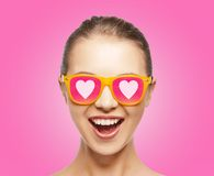 Amazed teen girl in sunglasses. Love, happiness and valentines day concept - amazed teen girl in sunglasses with hearts on pink background Stock Image