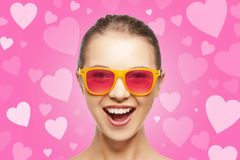 Amazed teen girl in sunglasses. Love, happiness and valentines day concept - amazed teen girl in pink sunglasses on background with hearts Royalty Free Stock Photography
