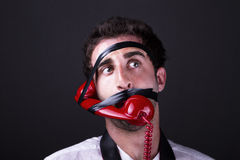 A amazed telephoneman. A man amazed with the phone tied to the face Stock Photography