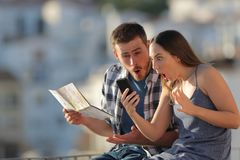 Amazed tourists finding online offers on vacation. Amazed tourists finding online offers sitting on a ledge on vacation in a town stock images
