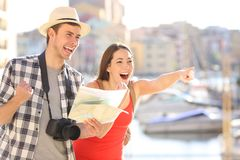 Amazed tourists finding and pointing landmark. Couple of amazed tourists finding and pointing landmarks outddor on summer vacation Stock Image