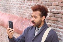 Amazed trendy man using his phone royalty free stock photo