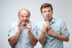 Amazed two mature men is shocked a little with news. Amazed two mature men son and father is shocked a little with news. Body language concept royalty free stock photo
