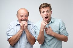 Amazed two mature men is shocked a little with news. Amazed two mature men son and father is shocked a little with news. Body language concept stock photo