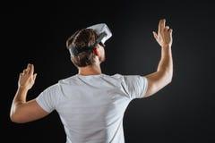 Amazed unshaken man tasting VR glasses an lifting hand. Interesting thing. Amazed unshaken interested man turning to a wall tasting VR glasses an lifting hand Stock Images