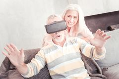 Amazed unshaken man using VR glasses and sitting on the sofa. New experience. Amazed unshaken aged men using VR glasses holding hands in front of himself and Stock Photo