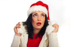 Amazed winter woman looking up. Amazed winter woman with Santa hat looking up and holding her fur jacket against white background Stock Photo