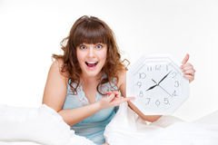 Amazed woman. Sitting in white bed and pointing at clock Stock Photos