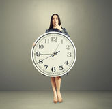 Amazed woman with big white clock Royalty Free Stock Photo