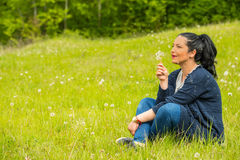 Amazed woman blowing dandelions Royalty Free Stock Image