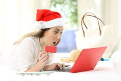 Amazed woman buying online on christmas holidays. Amazed woman buying online with a laptop and a credit card on christmas holidays royalty free stock images