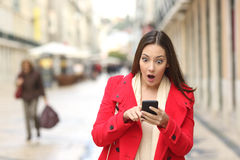 Amazed woman checking smart phone in the street. Front view of a fashion amazed woman checking smart phone in the street and walking towards camera Stock Photos