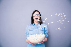 Amazed woman in cinema standing with bowl of popcorn Royalty Free Stock Image