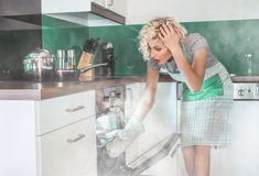 Amazed woman cook frying or roasting. Something in a oven. Smoke, vapor around in the kitchen or home Stock Photo