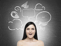 Amazed woman and dialogue boxes on blackboard Royalty Free Stock Photography