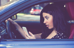 Amazed woman distracted reading a message on cellphone driving a car stock images