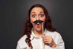 Amazed woman with fake mustache. Picture over dark background Stock Photo