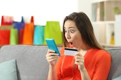 Amazed woman finding online offers holding credit card. Sitting on a couch in the living room at home Stock Photos