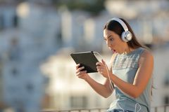 Amazed woman finds online content on a tablet. Sitting in a town at sunset stock images