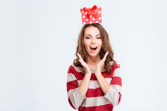 Amazed woman with gift box on head looking at camera Royalty Free Stock Photos
