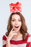 Amazed woman with gift box on head looking at camera Royalty Free Stock Photography