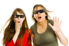 Amazed woman and girl in cinema wearing 3D glasses experiencing 5D cinema effect - scared watching performance - gestures of royalty free stock photography
