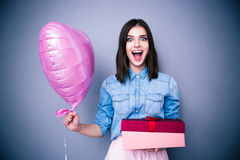 Amazed woman holding balloon and gift box. Over gray background. Looking at camera Stock Photo
