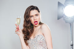 Amazed woman holding glass of champagne. And looking at camera Stock Photography