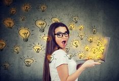 Amazed woman holding a laptop with brilliant ideas light bulbs flying out. Amazed young woman holding a laptop with brilliant ideas light bulbs flying out stock photos