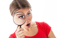 Amazed woman holding a magnifying glass Royalty Free Stock Photography