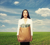 Amazed woman holding money. Amazed young businesswoman holding paper bag with money and looking at camera over green field and blue sky Royalty Free Stock Photography