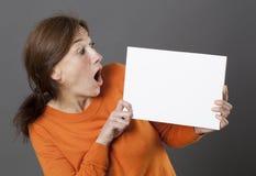 Amazed woman holding a panicking blank communication board to alert Stock Photo